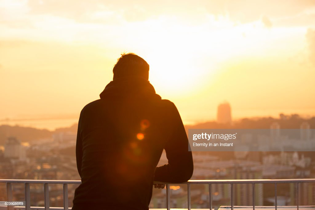 Man looking out over city at sunset : Stock Photo