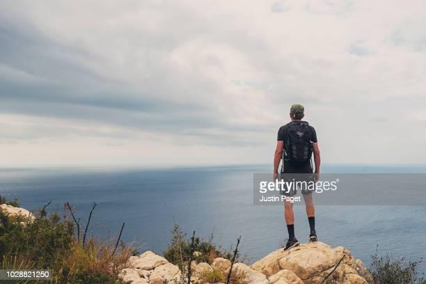 man looking out over mediterranean sea - pantaloncini grigi foto e immagini stock