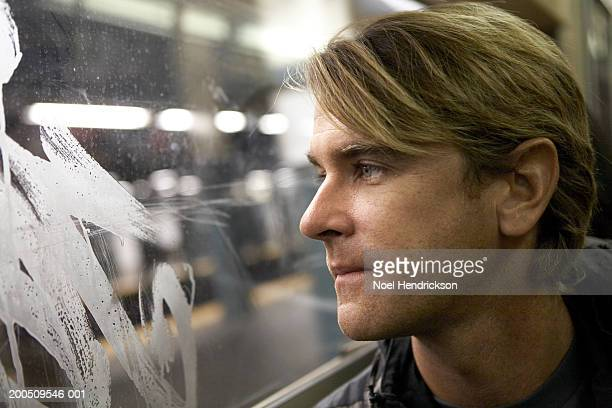 Man looking out subway window
