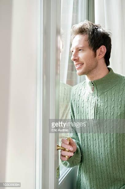 man looking out through a door glass - só um homem jovem imagens e fotografias de stock