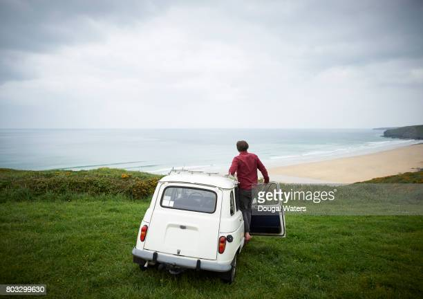 Man looking out to sea from car on Atlantic coastline.