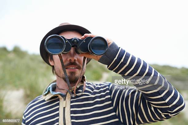 Man looking out to sea with binoculars.