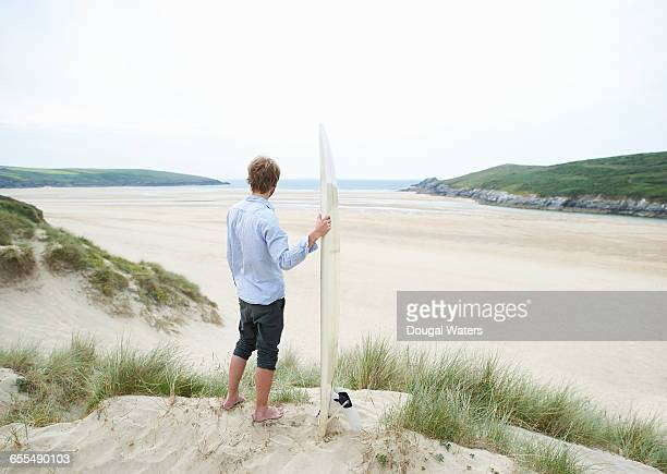 Man looking out to sea with surf board.