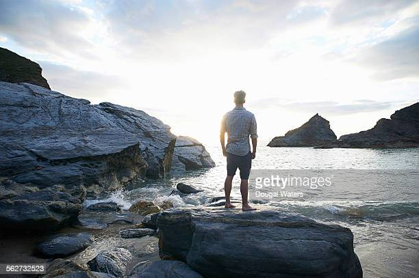 Man looking out toward sunset from rocky coast