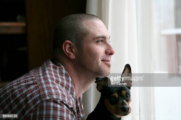 Man looking out window, dog looking at camera