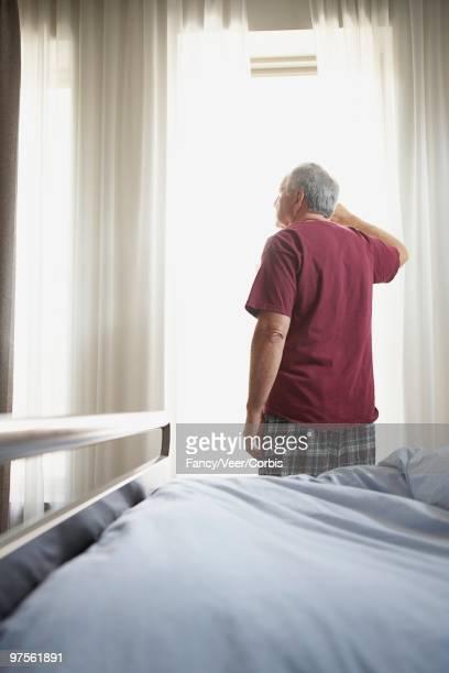 man looking out window - vieilles fesses photos et images de collection