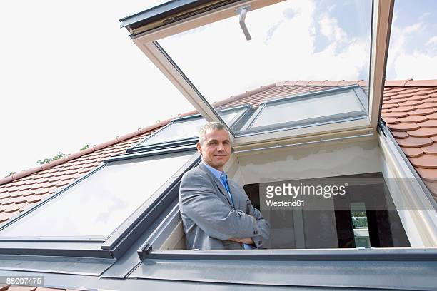 Man looking out dormer window, portrait