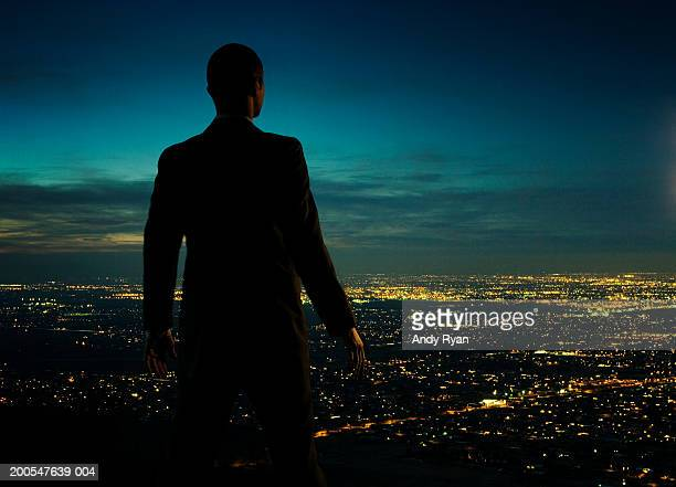 Man looking over cityscape at night, rear view