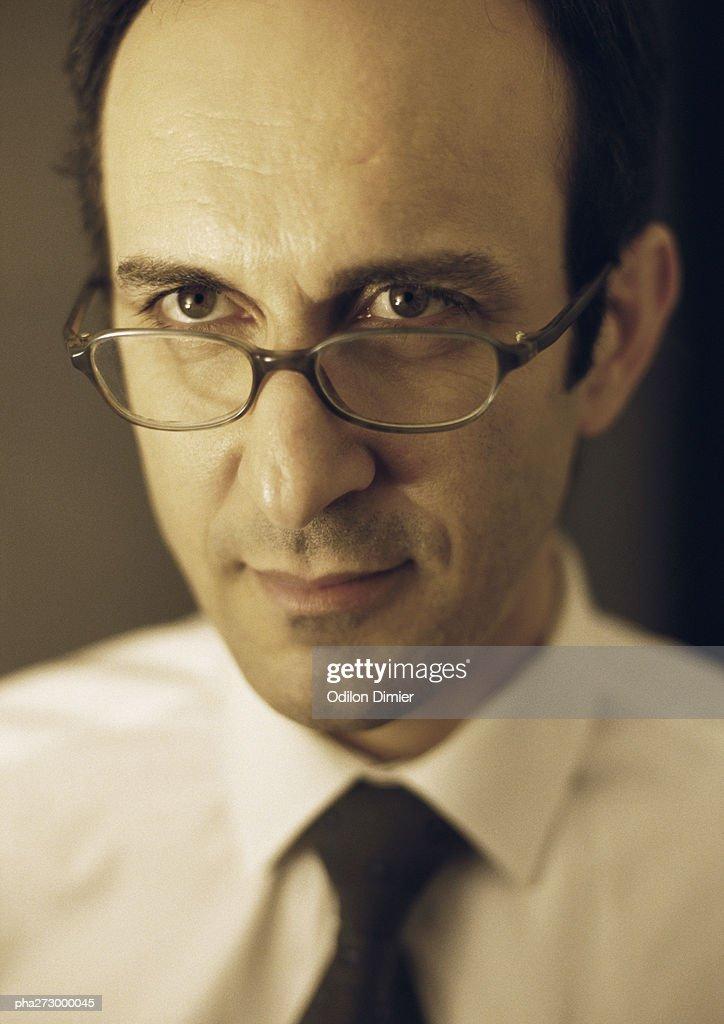 Man looking over edge of glasses, portrait : Stockfoto