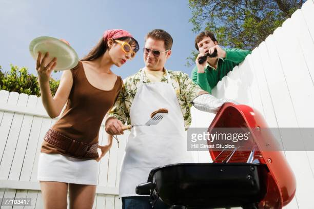 Man looking over fence at barbecue