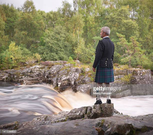 man looking over flowing river in traditional scottish prince charlie outfit with douglas modern tartan - kilt stock photos and pictures