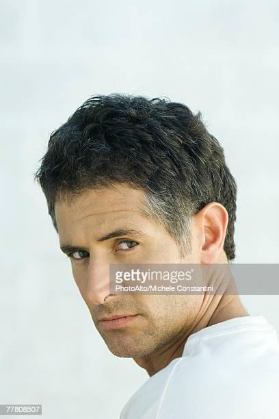 Man, looking over shoulder at camera, portrait