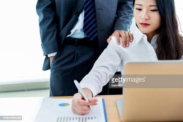 man die over de schouder op het werk van zijn vrouwelijke collega - ongewenste intimiteit stockfoto's en -beelden