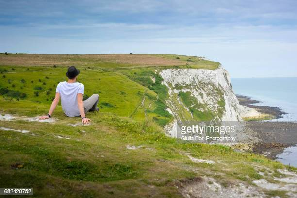 man looking over the white cliffs of dover - dover england stock pictures, royalty-free photos & images