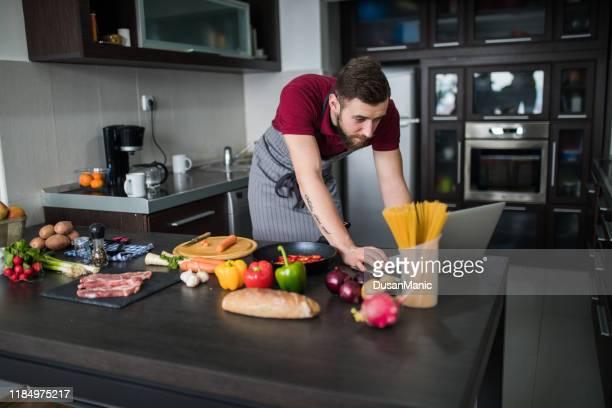 receita de vista do homem no portátil na cozinha em casa - só um homem - fotografias e filmes do acervo