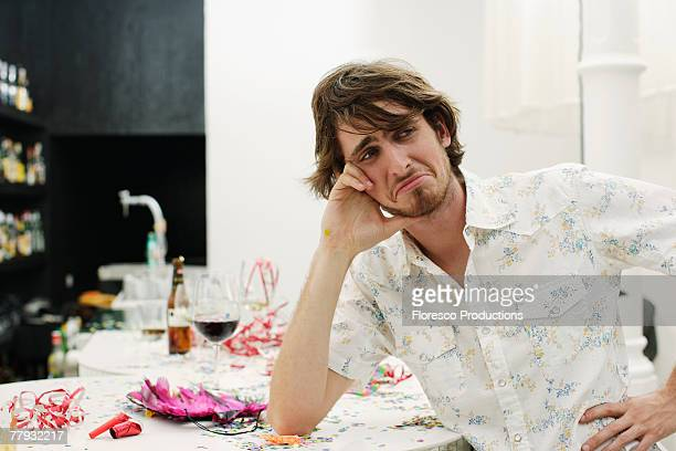 man looking sad leaning on table - after party mess stock pictures, royalty-free photos & images