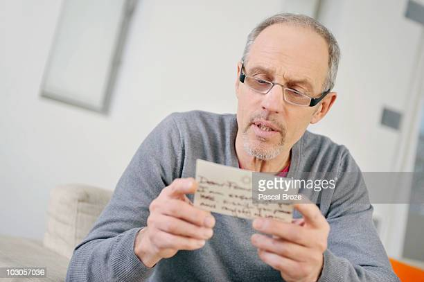 Man looking serious while reading a postcard