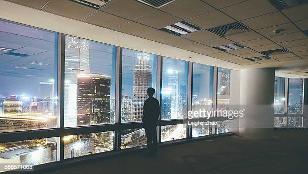 Man looking skyscraper at night