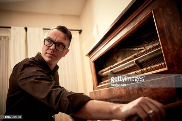 man looking suspicious at piano - heshphoto imagens e fotografias de stock