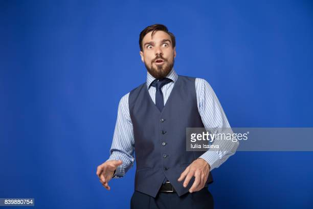 man looking terrified on blue background - überraschung stock-fotos und bilder