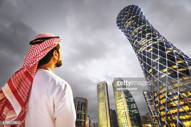 man looking the doha skyline in qatar - gulf countries stock pictures, royalty-free photos & images