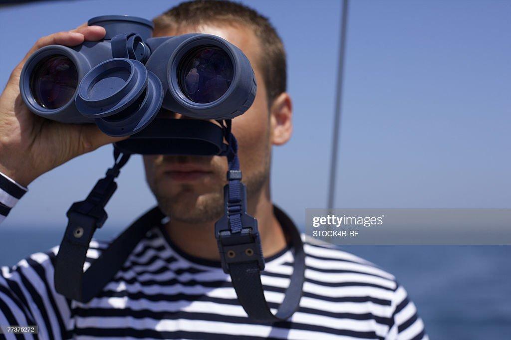 Man looking through a spyglass : Photo