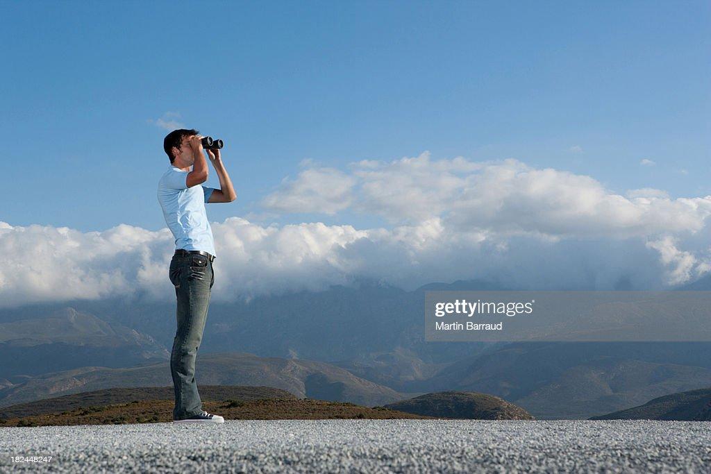 Man looking through binocular at outdoors : Stock Photo