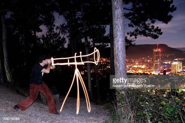 Man Looking Through Binoculars Created By Light Painting With Illuminated Cityscape In Background