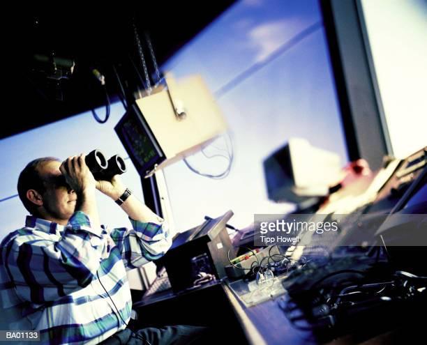 Man looking through binoculars in air traffic control room