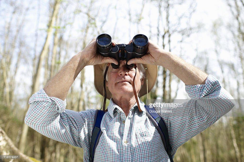 Man looking through binoculars in forest. : Stock Photo