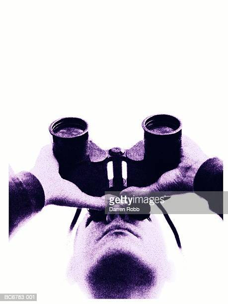 man looking through binoculars, low angle view, close-up (toned b&w) - binoculars stock pictures, royalty-free photos & images