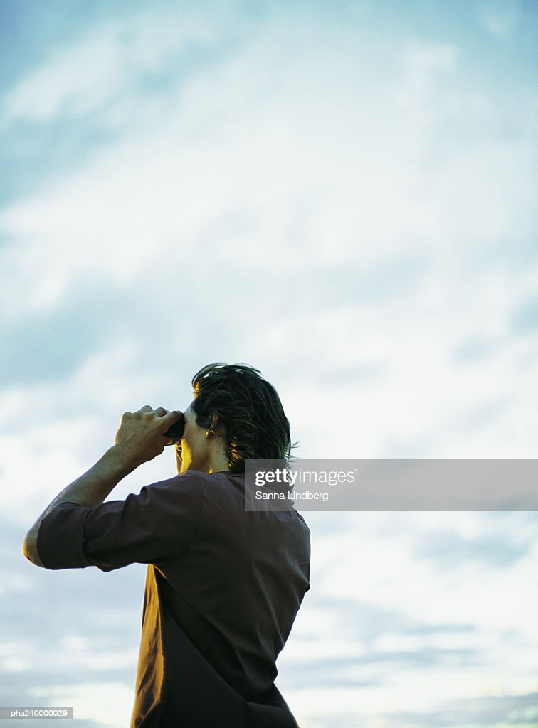 Man looking through binoculars, low angle view : Stockfoto