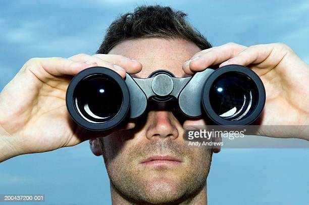 Man looking through binoculars outdoors, close-up