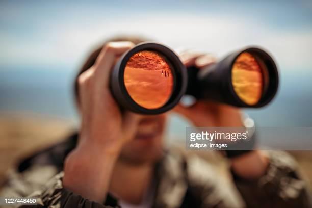 mens die door verrekijkers kijkt - verrekijker stockfoto's en -beelden