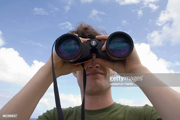 man looking through binoculars - jessamyn harris stock pictures, royalty-free photos & images
