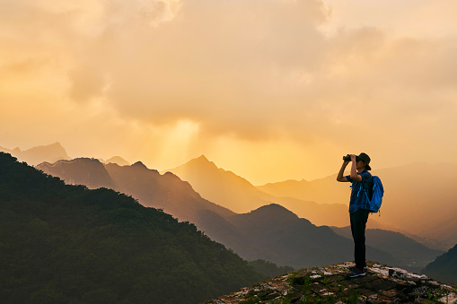 Man Looking Through Binoculars While Standing On Mountain Against Sky During Sunset - gettyimageskorea