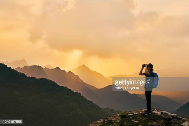 man looking through binoculars while standing on mountain against sky during sunset - binoculars stock pictures, royalty-free photos & images