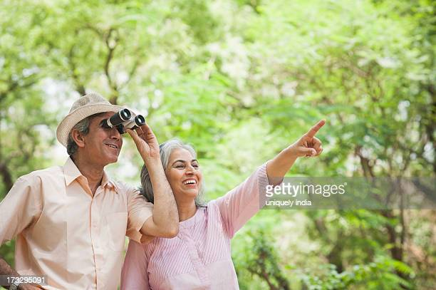 Man looking through binoculars with his wife standing beisde him and pointing, Lodi Gardens, New Delhi, India