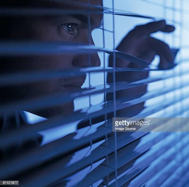 man looking through blinds - voyeurismo fotografías e imágenes de stock