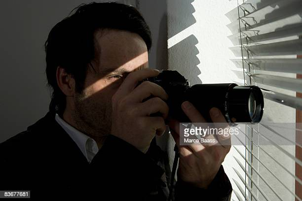 A man looking through blinds with a camera