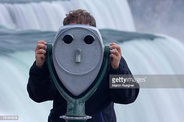 Man looking through coin-operated binoculars, Niagara Falls in background