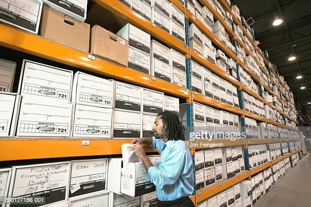 man looking through file boxes in warehouse - grupo grande de objetos - fotografias e filmes do acervo