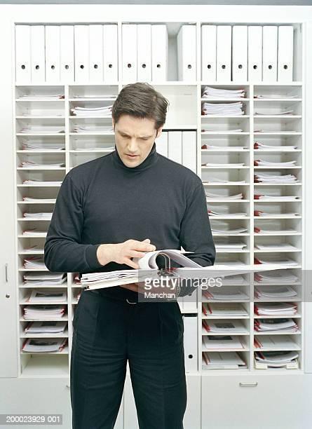 Man looking through file by pigeonholes