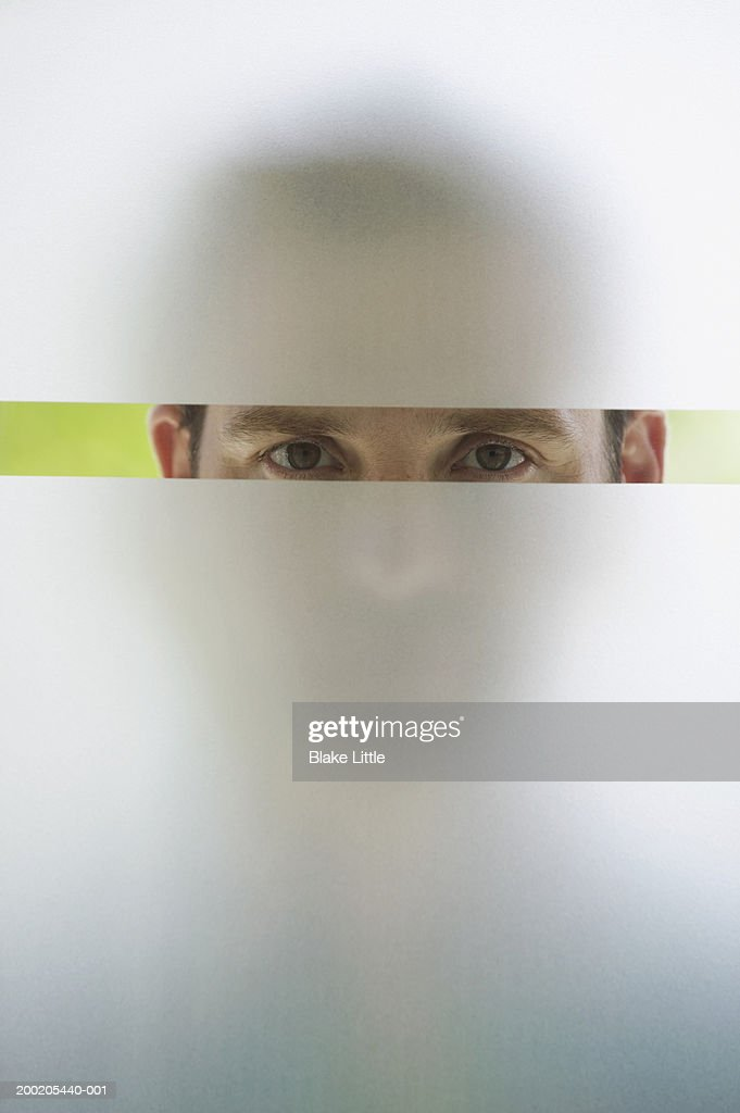 Man looking through frosted glass window, portrait (upper section) : Bildbanksbilder