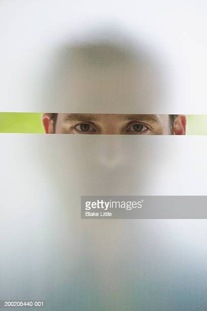 Man looking through frosted glass window, portrait (upper section)