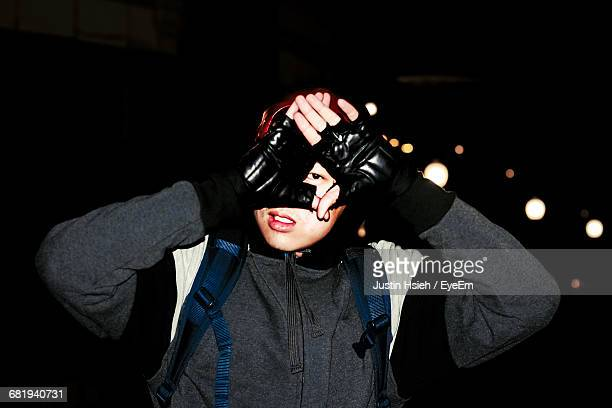 Man Looking Through Hands At Night