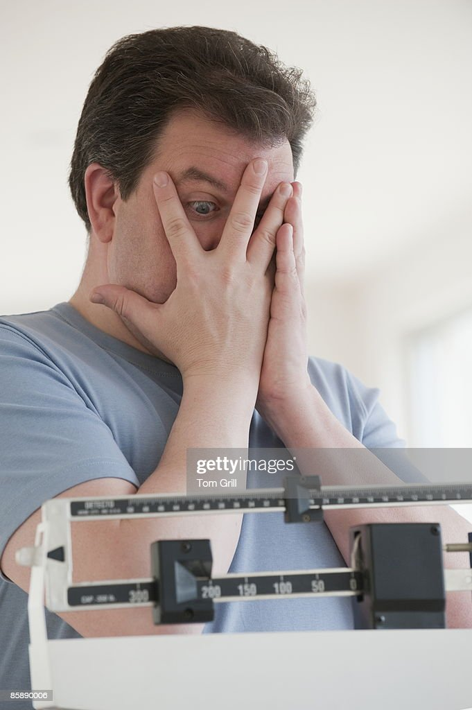 Man looking through hands at number on scale : Stock Photo