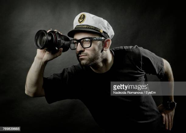 man looking through lens against wall - sailor hat stock pictures, royalty-free photos & images