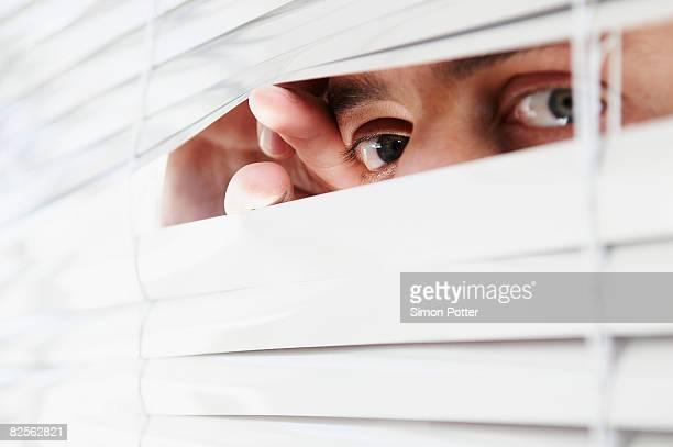 Man looking through office blinds