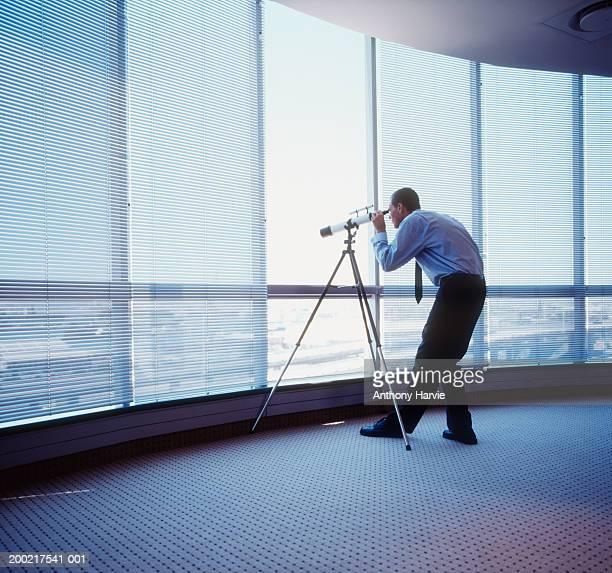 Man looking through telescope through office window